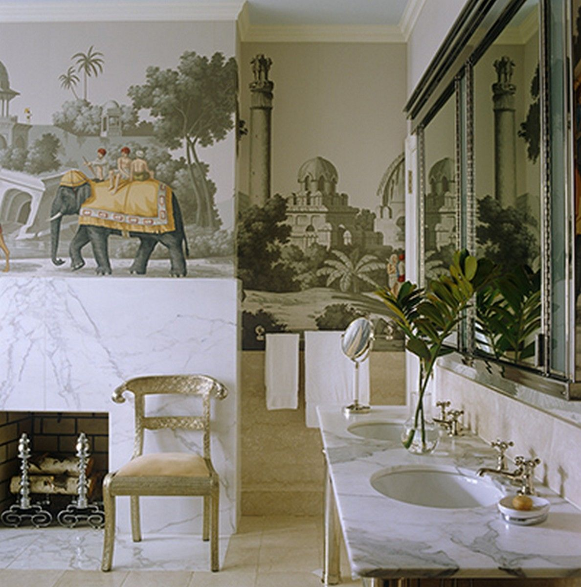 The walls of the bathroom are covered with a De Gournay Indian-themed papier peint with a touch of luxury coming from the grey marble fireplace and matching washstand